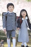 桜の下を歩く小学生男女