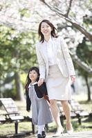 桜並木を歩く小学生女子と母親