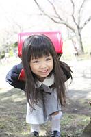 桜の下で微笑む小学生女子