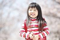 桜の下に立つ笑顔の小学生女子