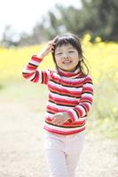 菜の花畑を歩く小学生女子