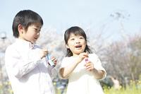 シャボン玉で遊ぶ小学生男女
