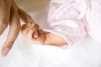 父親の小指を握る赤ちゃんの手元