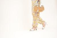 鞄をもって歩く女性の足元