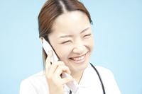 携帯電話で通話する看護師