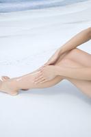 日焼け止めをぬる女性の脚