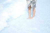 プールの波打ち際に立つ女性の足下