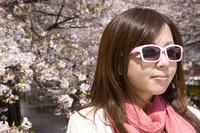 桜の下でサングラスをかける女性