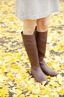 銀杏の葉の上に立つ女性の足元