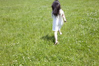草原を走る女の子の後ろ姿