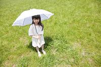 草原で日傘を差して微笑む女の子