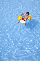 浮き輪でプールに浮かぶ水着姿の男の子