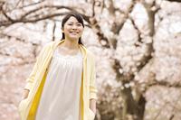 桜の下を散歩する女性