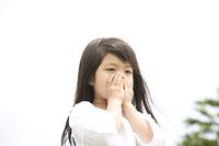 口を手で覆う女の子