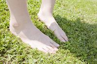 芝生に裸足で立つ女性の足下