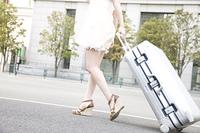 キャリーバックを引いて街中を歩く女性の足元
