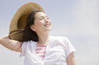 麦藁帽子を被って笑っている女性