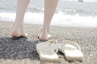 砂浜で素足になる女性