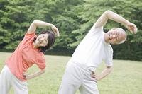 公園でラジオ体操をする老夫婦