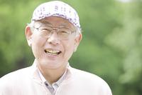 帽子を被りながら笑っている老人
