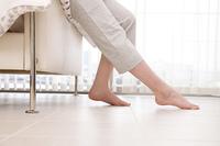 ベッドに腰をかけている女性の足元