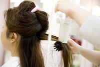 ドライヤーで濡れた髪を乾かす美容師の手元