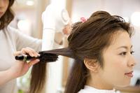 ドライヤーで美容師に髪を乾かしてもらう女性