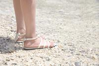 ビーチに立つ女性の足元