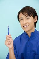 歯ブラシを持つ男性歯科医師