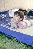 テントの中から外を見ている男の子