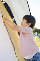 テントのファスナーを開け閉めする男の子