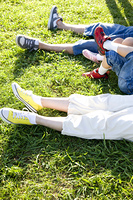 芝生に寝転ぶ家族の足元