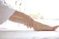 自分の足をマッサージする女性
