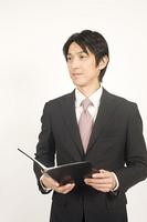 手帳を持っているビジネスマン