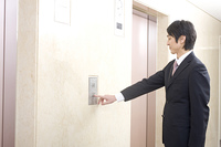 エレベーターのボタンを押すビジネスマン