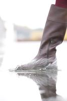 水溜りを歩く女性の足元