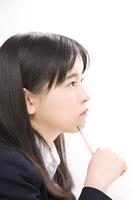 シャーペンを顎にあて考える女子中学生
