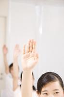 手を上げる男女の手元