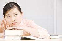 辞書の上に顔をのせる女の子