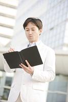 手帳を見るビジネスマン