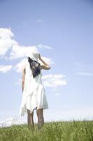草原に立つ女性の後ろ姿