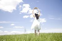 草原で両手を上げる女性の後ろ姿