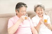 ソファに座りアイスティーを飲む老夫婦