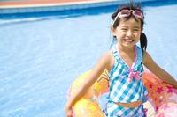浮き輪を持って微笑む水着姿の女の子