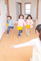 幼稚園教諭に向かって走る幼稚園児