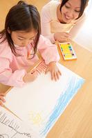 お絵描きを楽しむ幼稚園女児と見守る幼稚園教諭