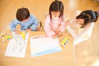 お絵描きを楽しむ幼稚園児と見守る幼稚園教諭