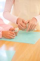 粘土で遊ぶ幼稚園女児と幼稚園教諭の手元