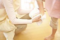 幼稚園女児の足を拭く幼稚園教諭