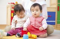 おもちゃで遊ぶ保育士と保育園児